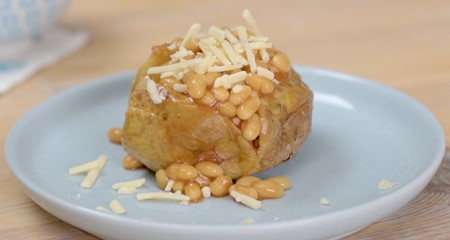A baked jacket potato on a plate topped with baked beans and grated cheese